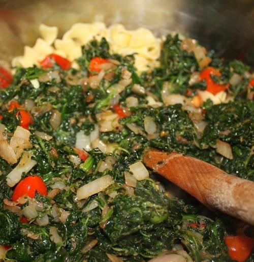 saute spinach tomato onions wooden spoon