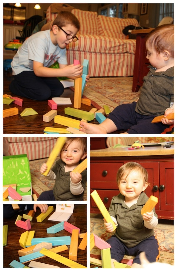 baby playing with tegu building blocks