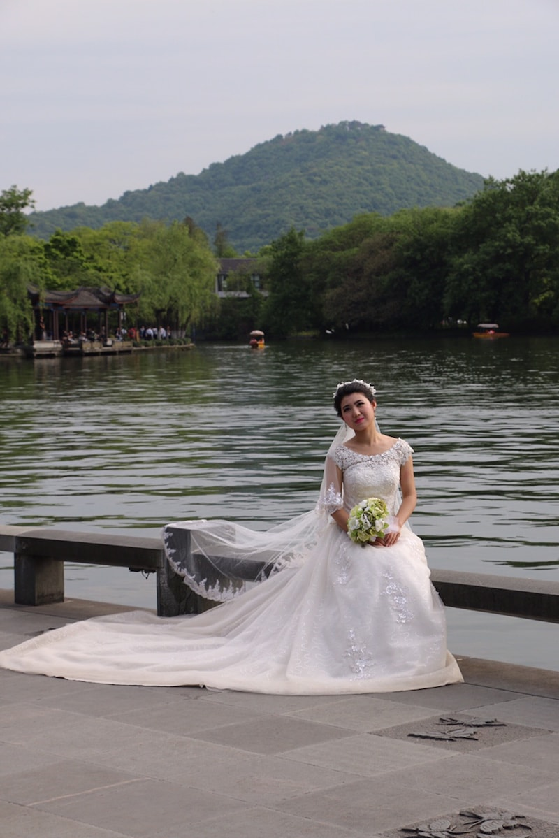 Chinese bride posing in her wedding dress by lake