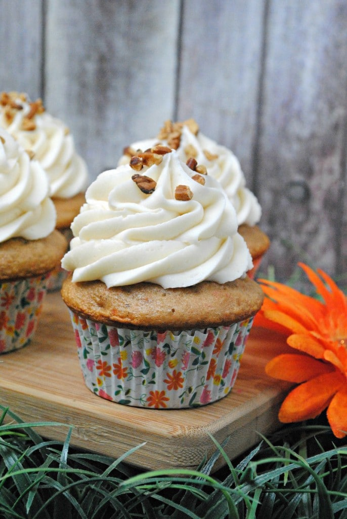 Chopped pecans on top of cream cheese frosted cupcakes