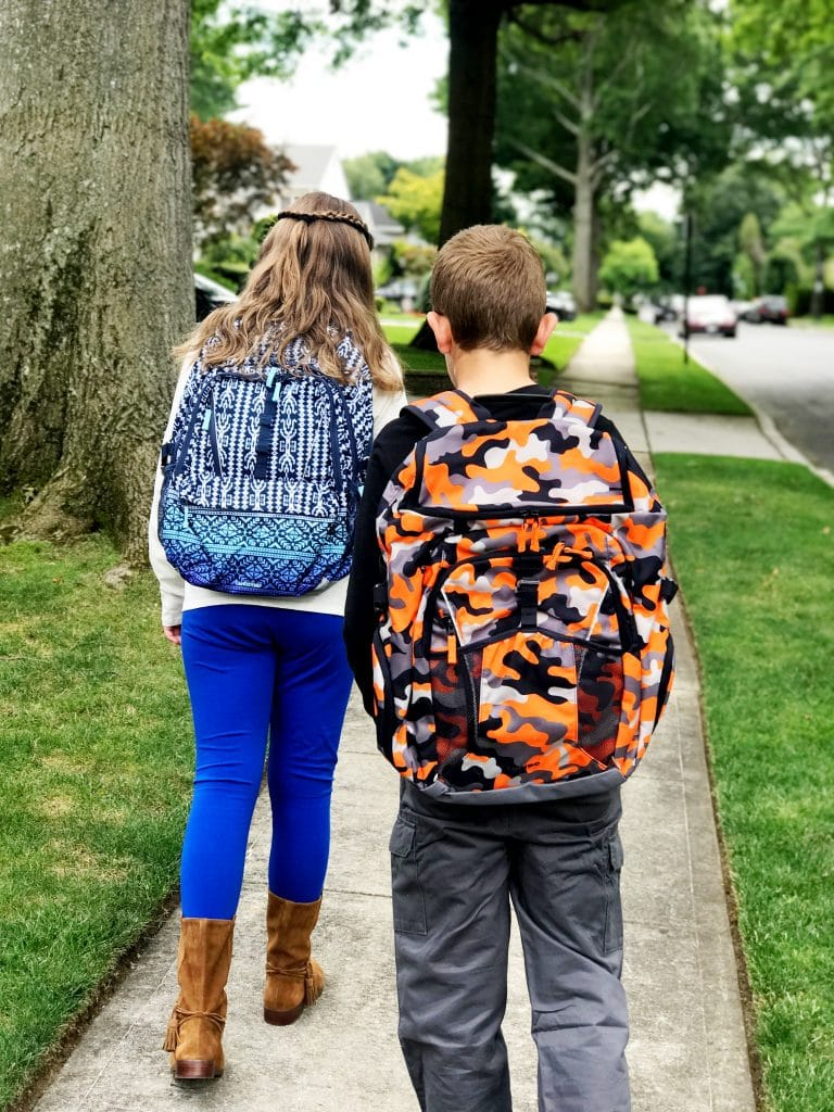 family walking to school with school bags on