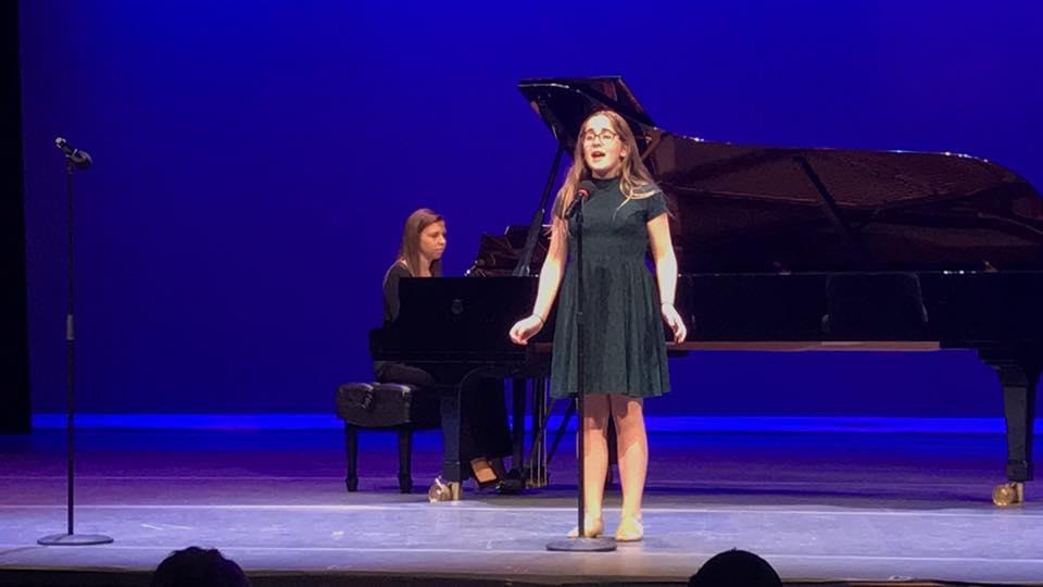 child on stage singing