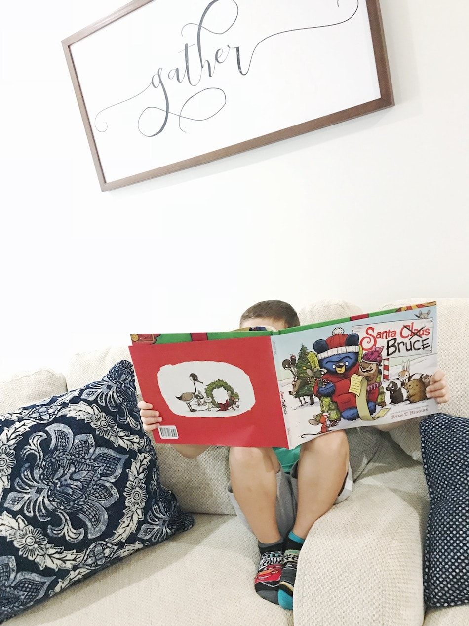 Boy reading Santa Bruce book on couch
