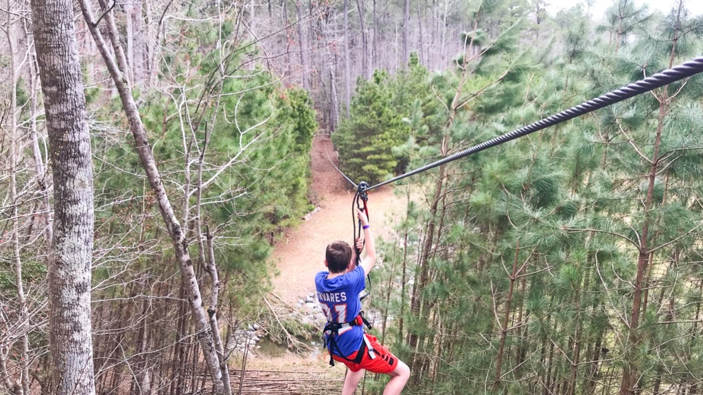 teen boy zip lining from the tree tops