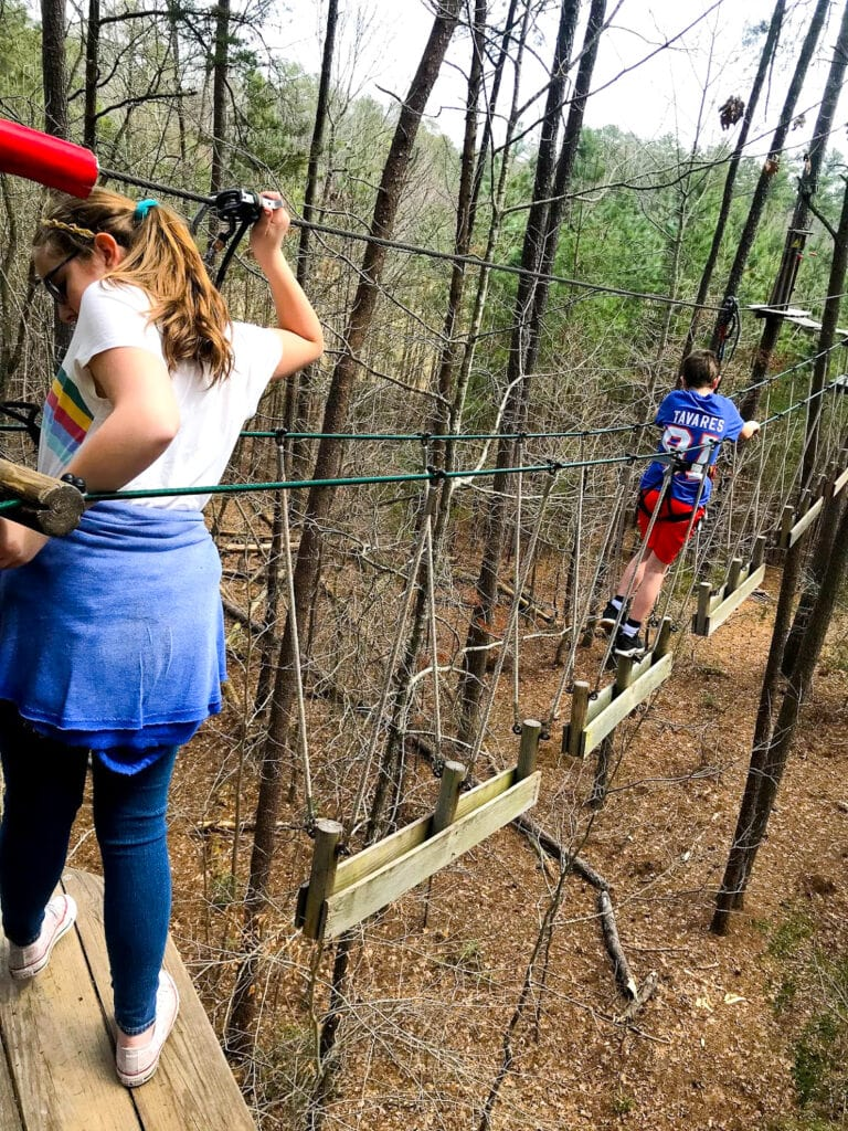 teens doing a tree obstacle course