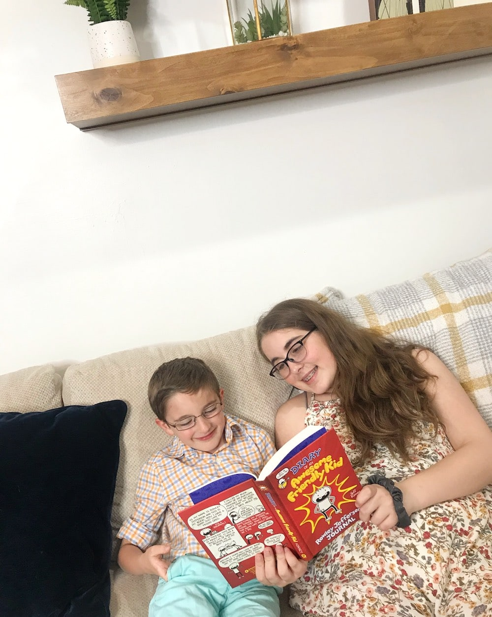 brother and sister reading Diary of an Awesome Friendly Kid on couch