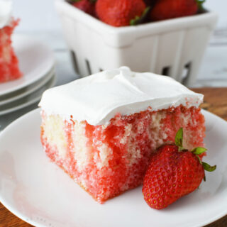 strawberry jello poke cake on a plate with strawberries in the background