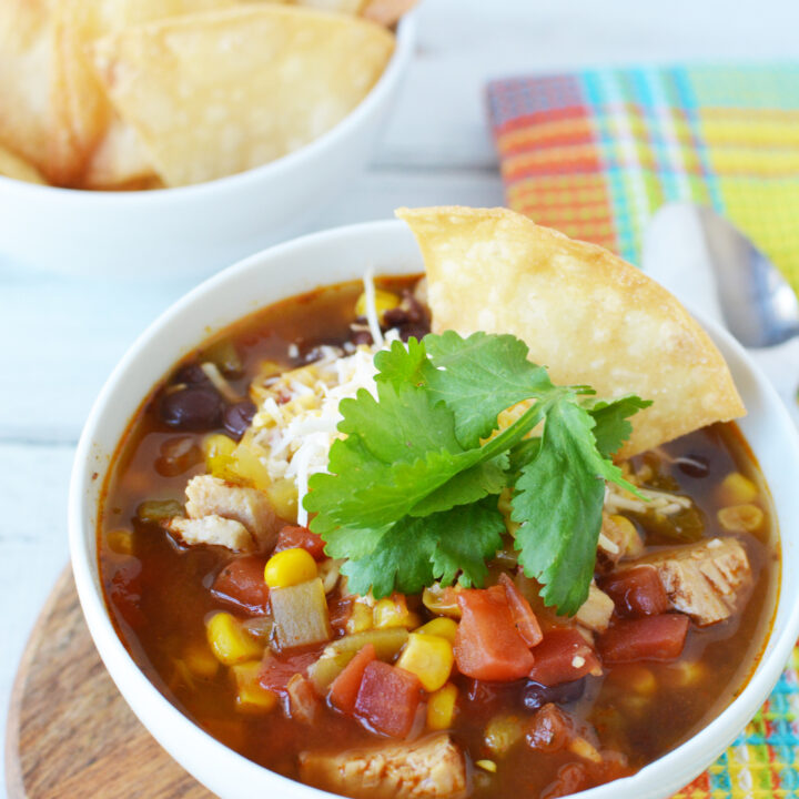 Chicken tortilla soup topped with cilantro and tortilla chips