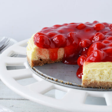 Cherry Cheesecake Recipe with a piece cut out on a cake stand